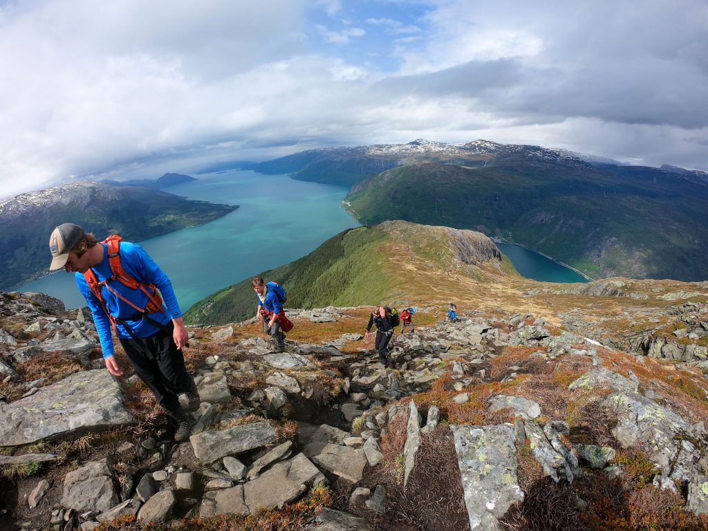 people hiking in norwaz view above fjord